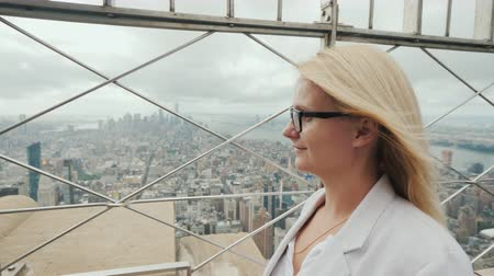 Side view of a woman admiring New York City from a high point