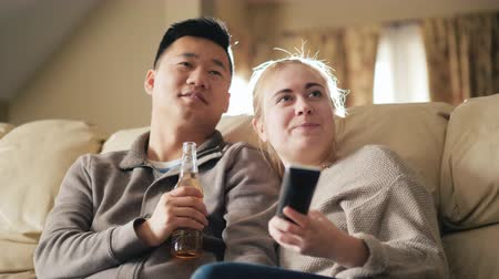 beer house : Young multiethnic family watching television together, man drinking a drink from a bottle