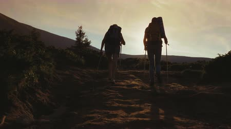 ambição : Two travelers with backpacks go forward along the mountain path towards the sun