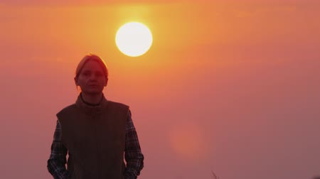 ninhada : A woman walks toward the camera, a large red sun shines from behind