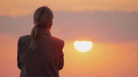 Woman looking forward to the setting red sun Стоковые видеозаписи