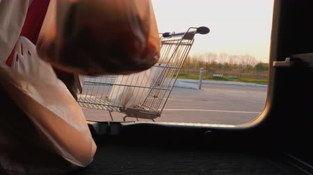 demanda : Woman puts shopping bags in the trunk of a car. View from inside the car Stock Footage