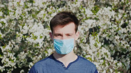 alergia : A man in a gauze bandage against a background of flowering trees. Allergy during the spring flowering concept