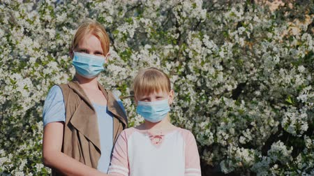 alergia : Woman with children in gauze bandages against the background of flowering trees. Allergy problems in the spring