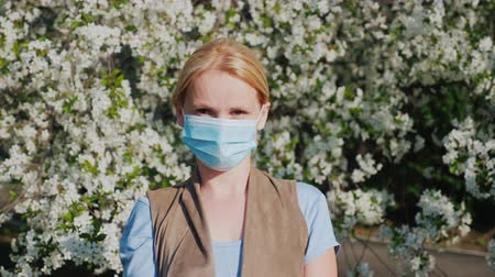 A man in a gauze bandage against a background of flowering trees. Allergy during the spring flowering concept