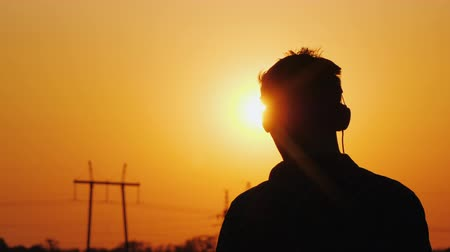 head over : Teenager in headphones listening to music, looking at a beautiful sunset over the city, view from behind