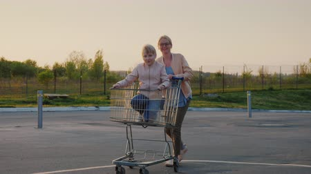 Mom rolls her daughter in a shopping basket