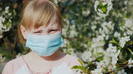 irritáció : Portrait of a child in a gauze bandage against the background of flowering trees. Allergy problems