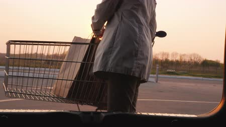 Womans silhouette, opens the trunk of a car, puts there paper shopping bags