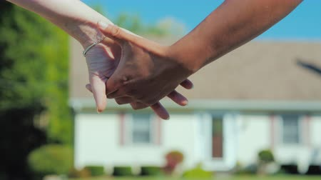 homeopático : A young couple takes each others hands against the backdrop of their new dream home. Buying real estate concept Stock Footage