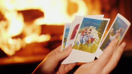 Woman looking at photos from vacation. In the photo, a young couple is resting in the mountains, in the frame you can see only hands on the background of the fireplace