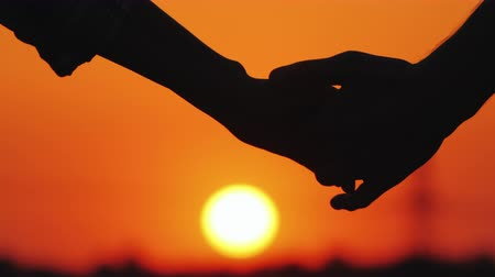 tomar : A young couple gently holding hands on the background of a large orange sun disc Vídeos