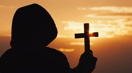 crucifixo : A monk in a hood with a crucifix in his hands stands against the backdrop of a dramatic sky at sunset Stock Footage