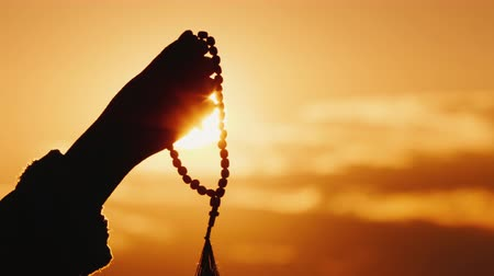 crucifixo : Hand holds rosary against the sky and the setting sun, sincere prayer and meditation