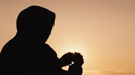 crucifixo : Silhouette of a man in the hood, sifting through the rosary at sunset