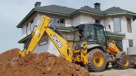 earthworks : Poltava, Ukraine, May 2019: Excavator digs a hole for laying communications against the background of a modern two-story house