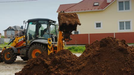 dragueur : Poltava, Ukraine, May 2019: Excavator digs a trench near private cottages