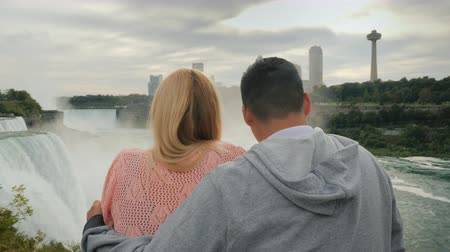 divu : A young multi-ethnic couple looks at the famous Niagara Falls, enjoying the popular tourist attraction
