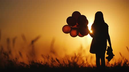 resmedilmeye değer : Silhouette of a girl with balloons and a teddy bear. It is worth the sunset. Farewell to childhood concept