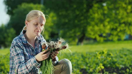 bastião : Woman holding fresh green onions, just plucked from the garden
