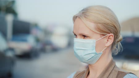 respirator : A woman in a protective gauze bandage stands near a dusty dirt road. Environmental problems
