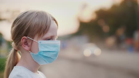 respirator : A child in a protective gauze bandage stands near a dusty highway. Health and ecology problems