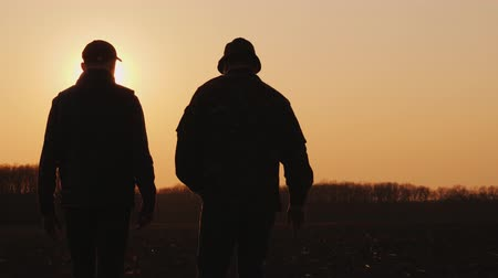 agronomist : Two farmers go across the field at sunset, the beginning of the sowing company