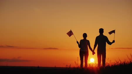 atender : A young couple with the flags of the United States in their hands admires the beautiful sunset. Independence Day concept Stock Footage