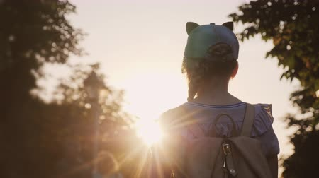 без вести пропавшие : A child with a backpack is standing in the park, the setting sun shines on him