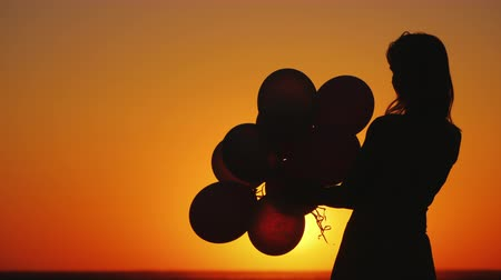 воздушный шар : Silhouette of a young woman with balloons at sunset