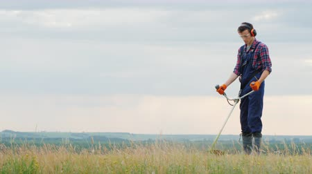 Young man mowing grass with a trimmer on a picturesque meadow