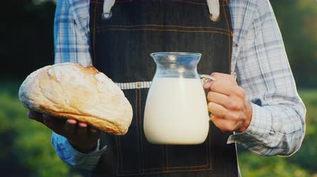 A man is a farmer holding a glass jug with milk and a loaf of bread