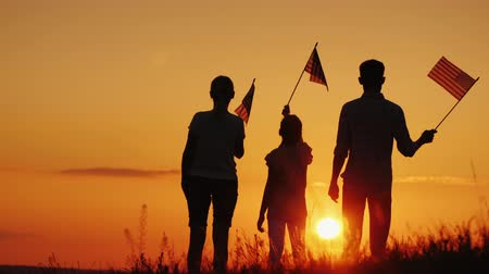 A family with American flags in their hands meets the dawn. Independence Day Celebration