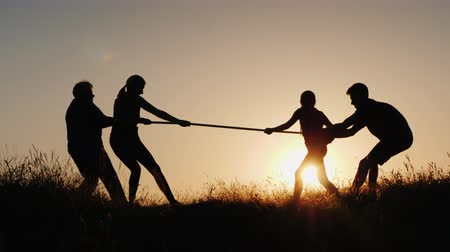egemen : Family having fun in nature - playing tug of war