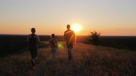 A young couple with a child jogging outdoors in scenic location on the sunset