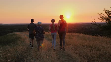Several generations of a family running together in a beautiful location