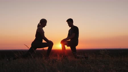 squat : Mom and her adult son play sports together in a beautiful sunset setting