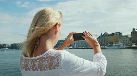 stockholm : A young woman photographs a beautiful view of the city of Stockholm. Travel in sweden Stock Footage