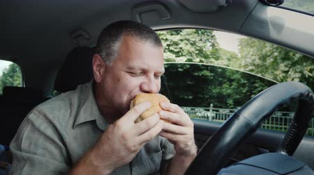 The driver eats fast food inside the car