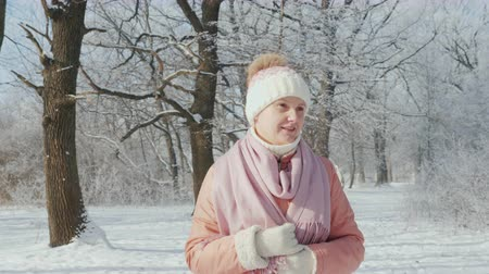 A middle-aged woman is walking in a winter park on a clear day, its snowing Filmati Stock