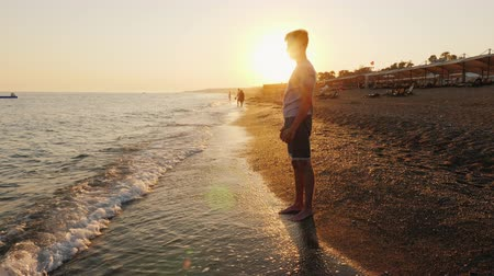 Young man stands on the beach, admires the sunset Стоковые видеозаписи