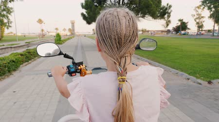 motorino : A child with African pigtails riding a scooter, rear view. Cheerful and active recreation