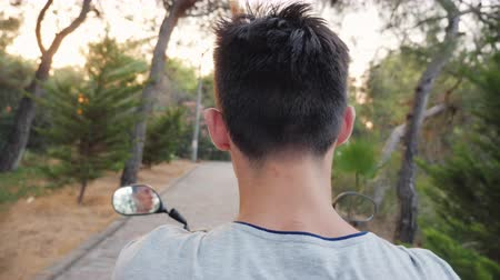 pigtailler : Rear view of a teenager riding a scooter