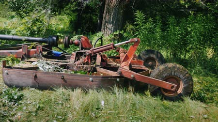 Side vie of The tractor pulls the grass mowing unit