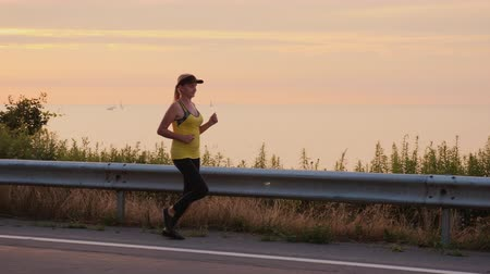 Woman makes an evening jog along the road along the lake