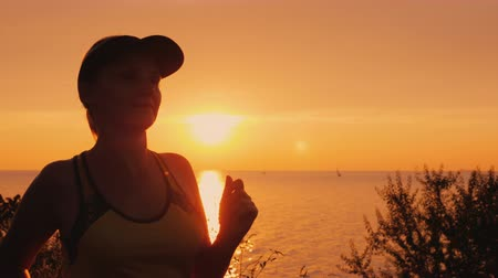 Healthy young woman jogging in the background of the sea and the setting sun