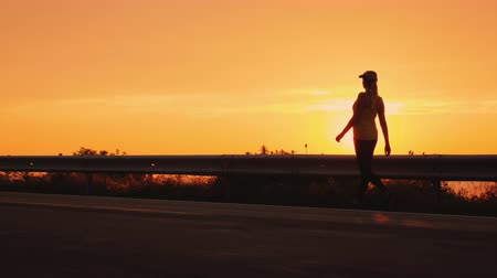 Heel-and-toe walk in a beautiful place. Silhouette of a woman walking along the road against the setting sun