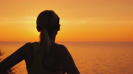 hayran olmak : Purposeful female athlete looks at the sunset over the sea, rear view Stok Video