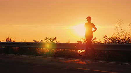 A young woman runs along the road along the seashore at sunset. Silhouette of an unrecognizable person