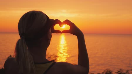 patria : A woman looks at the sea where the sun sets, shows a heart-shaped figure
